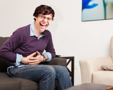 laughing man Profile view of a guy touching his belly and having a stomach ache at home