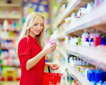 Beautiful woman choosing personal care product in supermarket shopping