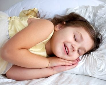 Happy smiling kid sleeping and smiling in her sleep. Dream the little princess on a white bed close-up speaking in dream.