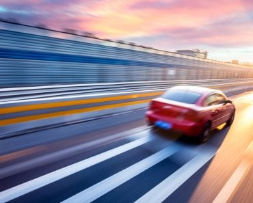 Car driving on freeway at sunset, motion blur full speed