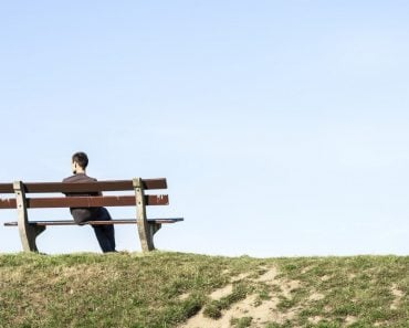 Young man sitting alone on bench