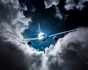 Passenger Airliner flying in the clouds airplane