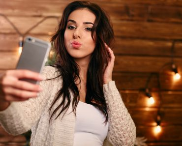 Portrait of a beautiful brunette taking a selfie with her smart phone at home Narcissism