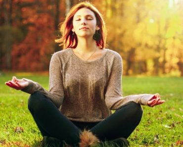 Young woman Zen meditate in park.