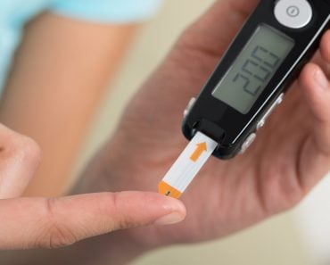 Young woman using glucometer to check blood sugar level at home Diabetes