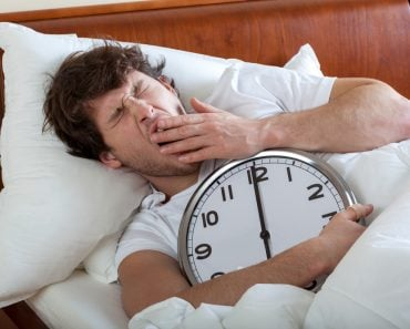 Man holding a big clock and waking up