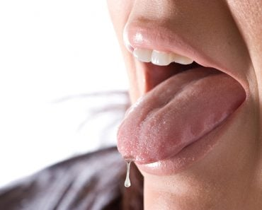 Closeup of a young woman sticking out her tongue saliva