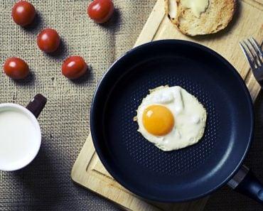 Frying egg in teflon cookware pan breakfast morning