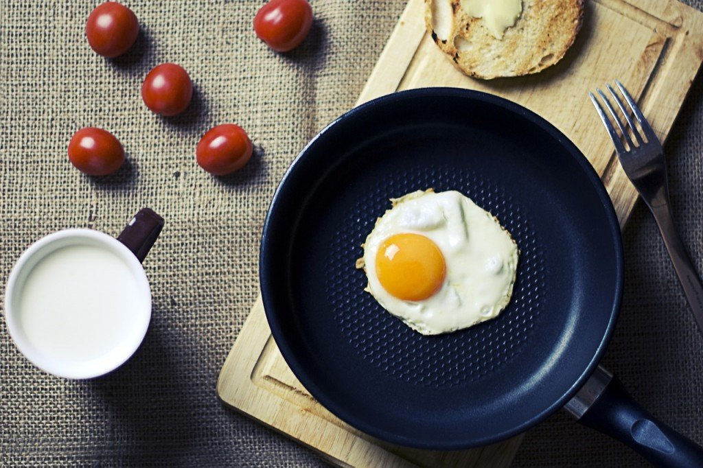 Frying egg in teflon cookware pan breakfast morning
