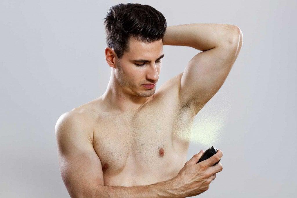 Handsome man spraying deodrant (InesBazdar)(s)