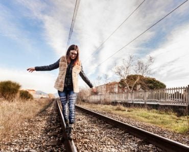 Beautiful Young Woman Walking in Balance on Railway Tracks. The Railroad is in a Residential Area. The Girl has a Casual Look.
