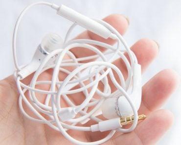 Woman's hand holds white tangled headphones isolated over white background (zazdravnaya)(s)