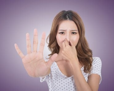 Portrait of a young woman holding her nose because of a linger bad smell girl. (elwynn)(s)