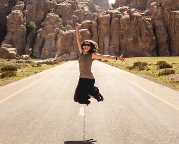 Woman jumping in midle of road