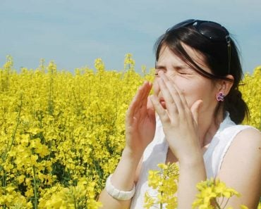 Pollen allergy, girl sneezing in a field of flowers sick