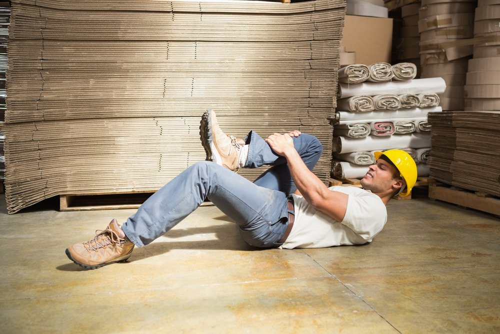 Side view of male worker lying on the floor in warehouse man hurt ouch.jpg