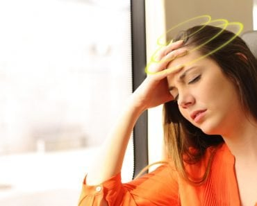 Passenger traveling and feeling dizzy with headache in a train travel sickness