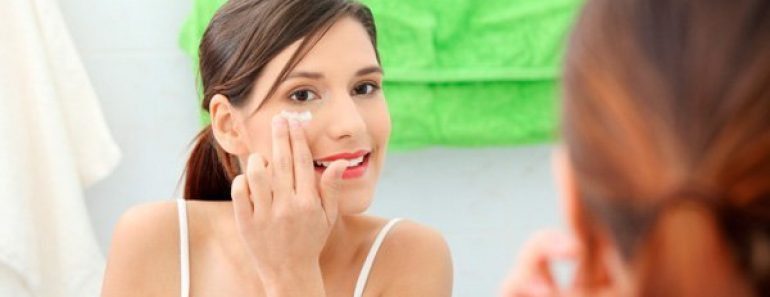 Girl applying lotion on face