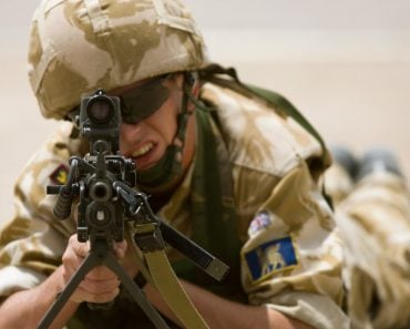 A British soldier aims a LMG