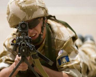 A British soldier aims a LMG