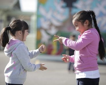 Two little girls playing Rock paper scissor playing children
