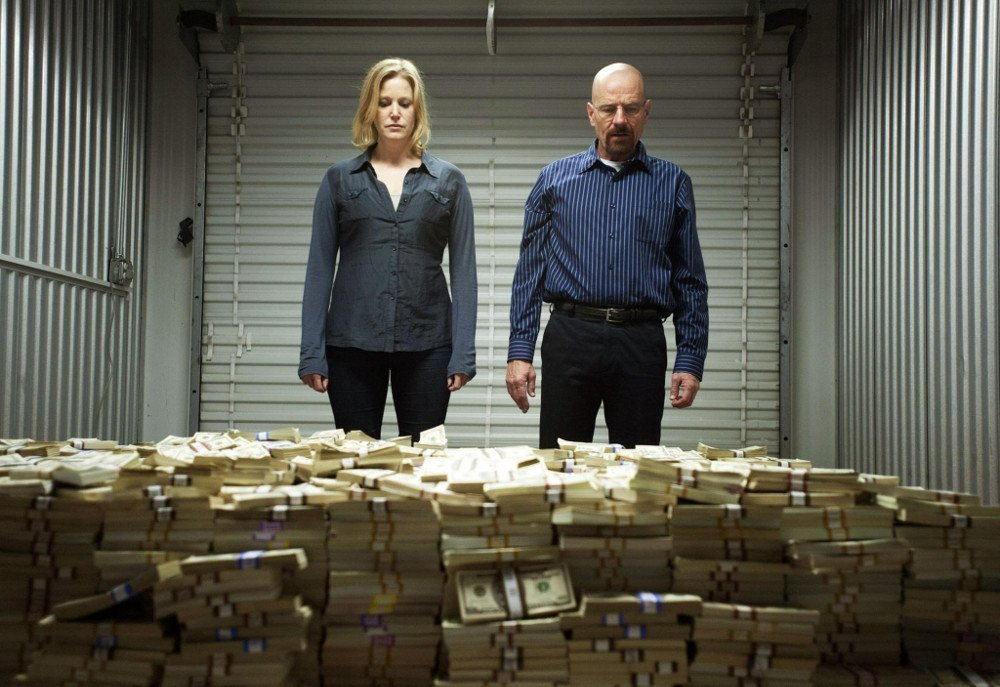 Breaking bad scene where Walter White and Skylar stand in front of a huge pile of cash