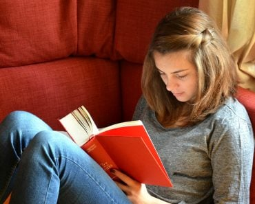 Young girl reading orange cover book on sofa