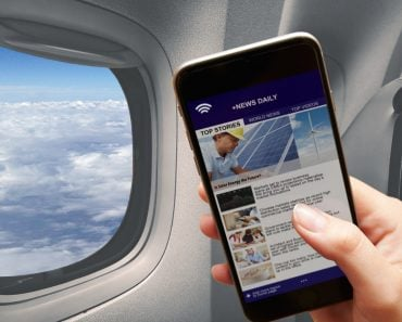 Mobile in girl hand reading news connected to the airplane wifi window cloud flying