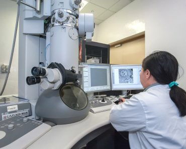 Scientists watching in electron microscope