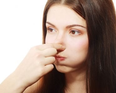 Young Woman Holding her Nose smelling something stinking popping ear