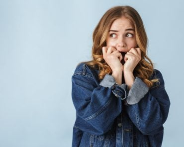 Attractive scared young girl standing isolated over white background, screaming - Image( Dean Drobot)s