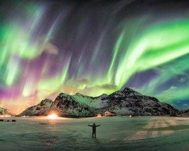 Aurora borealis (Northern lights) over mountain with one person at Skagsanden beach, Lofoten islands, Norway - Image(Mumemories)S