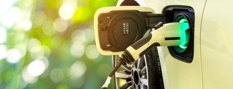 EV Car or Electric car at charging station with the power cable supply plugged in on blurred nature with soft light background. Eco-friendly alternative energy concept - Image(Smile Fight)s