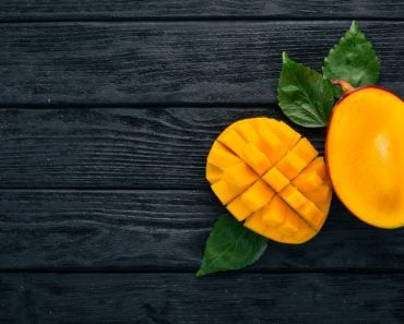 Mango. Tropical Fruits. On a wooden background. Top view. Copy space. - Image( YARUNIV Studio)s