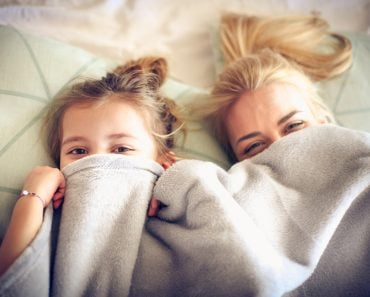 Portrait mother and daughter hide under blanket on a bed. - Image(Liderina)s