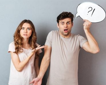 Portrait of a young frustrated couple having an argument while standing and holding speech bubble isolated over gray wall - Image(Dean Drobot)s