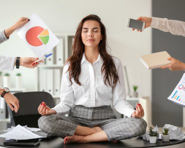 Businesswoman with a lot of work to do meditating in office - Image( Pixel-Shot)S