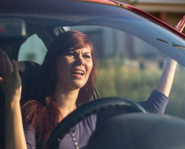 Closeup portrait, angry young sitting woman pissed off by drivers in front of her and gesturing with hands. Road rage traffic jam concept - Image(perfectlab)s