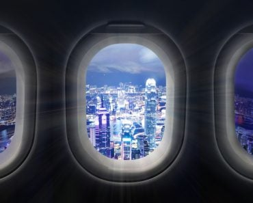 Composite image of city at night through airplane window - Image(ymgerman)S