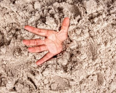 Hand on a beach sinking or drowning in quicksand - Image(Anneka)s