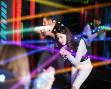 Portrait of girl in colored beams of laser guns during laser tag game on dark arena - Image( Iakov Filimonov)s