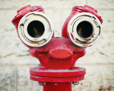 Red old fire hydrant on a street, looking like a face. Instagram style. Pareidolia. - Image(DG Stock)s