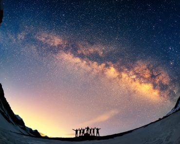 Teamwork and support. A group of people are standing together holding hands against the Milky Way in the mountains. - Image( Anton Jankovoy)S