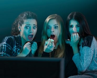 Teenage girls watching horror movie with popcorn - Image(iko)S