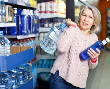 Tense modern woman lifting heavy bottle of still water while shopping at grocery store - Image( Iakov Filimonov)s