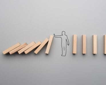 Wide cropped image of the outline of a businessman stopping the domino effect on gray background. - Image(Gajus)s