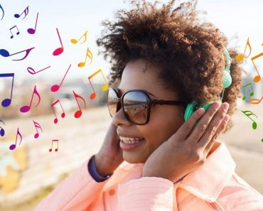 technology, lifestyle and people concept - smiling african american young woman or teenage girl in headphones listening to music outdoors over colorful musical notes background - Image( Syda Productions)s