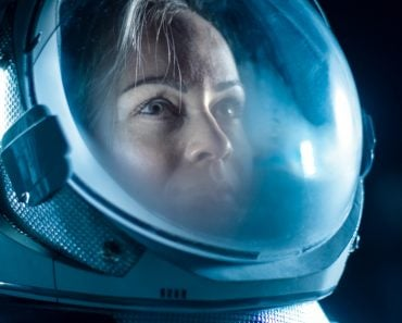Female Astronaut Wearing Helmet in Space, Looking around in Wonder(Gorodenkoff)S