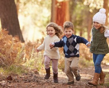 Group Of Young Children Running Along Path In Autumn Forest - Image(Monkey Business Images)s