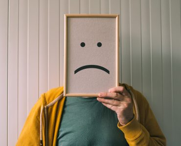 Put a sad pessimistic face on, sadness and depressive emotions concept, man holding picture frame with smiley emoticon printed. - Image(igorstevanovic)s
